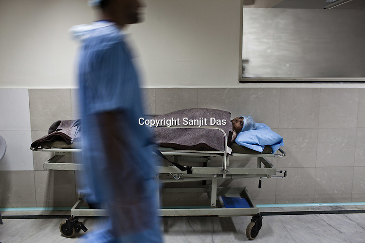 An attendant walks past a patient as she lies on the stretcher outside the Operation Theatre of the Narayana Hrudayalaya in Bangalore, Karnataka, India. Photo: Sanjit Das/Panos