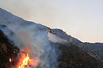 Flames burn on a hillside as a helicopter drops water in Malibu Canyon, Malibu, California October 21, 2007. The wildfire fanned by powerful winds burned out of control on Sunday in the celebrity seaside enclave of  Malibu, forcing hundreds of people to flee and destroying a handful of multimillion-dollar homes. Photo by Nina Prommer/Milestone Photo.