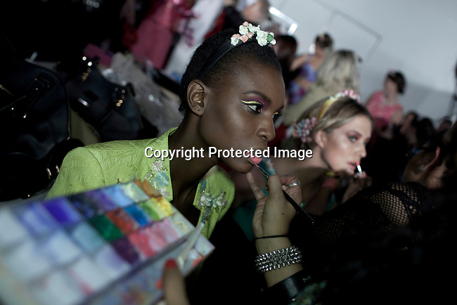 CAPE TOWN, SOUTH AFRICA - JULY 26: A model has her makeup done backstage before a fashion show with the designer label Gavin Rajah at the Mercedes Benz Cape Town Fashion Week on July 26, 2012, in Cape Town, South Africa. Some of South Africa's finest designers showed their 2012-13 spring and summer collections during the 4-day event. (Photo by Per-Anders Pettersson)