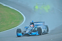 IZOD Indy Car Series rookie Rubens Barrichello, of the Brazil, negotiates a wet corner during a practice session Friday afternoon at Barber Motorsports Park in Birmingham, Alabama.