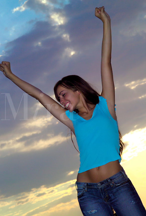 Beautiful female outdoors against the sky with her arms in the air.