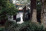 STATUE OF MONK OUTSIDE MONASTERY SURROUNDED BY FOLIAGE