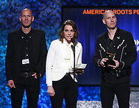 "Phil Hanseroth, from left, Brandi Carlile and Tim Hanseroth accept the award for best American roots performance for ""The Joke"" at the 61st annual Grammy Awards on Sunday, Feb. 10, 2019, in Los Angeles. (Photo by Matt Sayles/Invision/AP)"