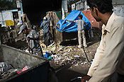 Sweepers work together to clear out garbage outside a local market in Govind Puri, New Delhi, India. Photo: Sanjit Das/Panos