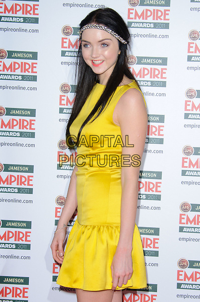 LILY COLE .Attending  the Jameson Empire Film Awards at the Grosvenor House Hotel, Park Lane, London, England, UK,.March 27th 2011..half length yellow dress headband head hair band hairband  sleeveless smiling .CAP/CJ.©Chris Joseph/Capital Pictures.