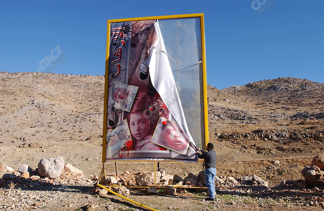 Hezbollah worker tried to straighten an anti-Israeli poster that had fallen down, barely more than a hundred yards from the Lebanese-Israeli border.<br />