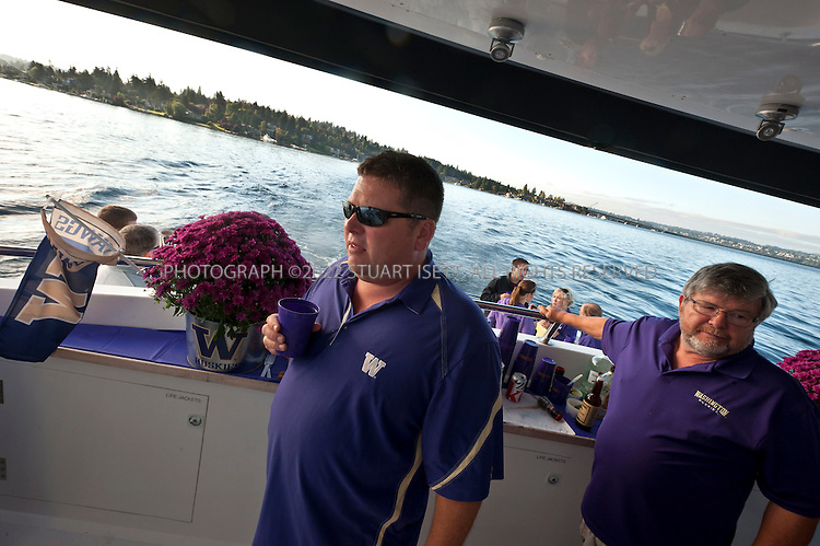 9/24/2011--Seattle, WA, USA...The Big Dawg's bartender Dick Wooding (right) and his son Tom Wooding (left)...The 'Big Dawg', owned by Lisa and Tim Kittilsby, is the biggest, most prominent boat that attends regular boat tailgate parties on docks near the UW (University of Washington) Husky Stadium. Up to 500 boats will tie up outside Husky Stadium on football game days, ranging from from small boats to huge yachts. The Big Dawg is a 92-foot, two-story yacht that dominates the tailgate parties...The tradition started when Lisa and Tim Kittilsby's parents, Frank and Jeanie Miles, took a 23-foot boat called The Mixer to a game over 40 years ago...©2011 Stuart Isett. All rights reserved.