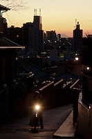 A moped climbs the street during sunset over Fujimizaka (Mount Fuji viewing Hill) in Nishi Nippori, Tokyo, Japan. Friday January 11th 2013. This is the last street level place in central Tokyo to see Mount Fuji and is threaten with development that will block the view of this iconic peak.
