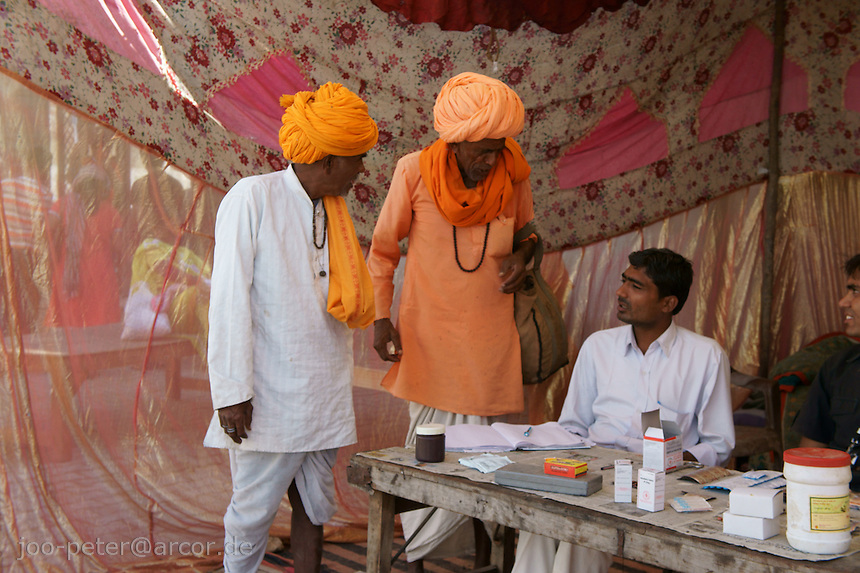 desert village people visiting camel fair in holy city Pushkar, Rajastan, India make a stop at a medical post. Saffron-colour turbans are worn by Rajputs.