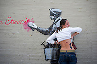 """A street art enthusiast shows off her Banksy inspired tattoo in the Woodside neighborhood of Queens in New York on Monday, October 14, 2013 in front of the fourteenth installment of Banksy's graffiti art, """"What we do in life echoes in Eternity"""". The elusive street artist is creating works around the city each day during the month of October accompanied by a satirical recorded message which you can hear by calling the number 1-800-656-4271 followed by  # and the number of artwork.  (© Frances M. Roberts)"""