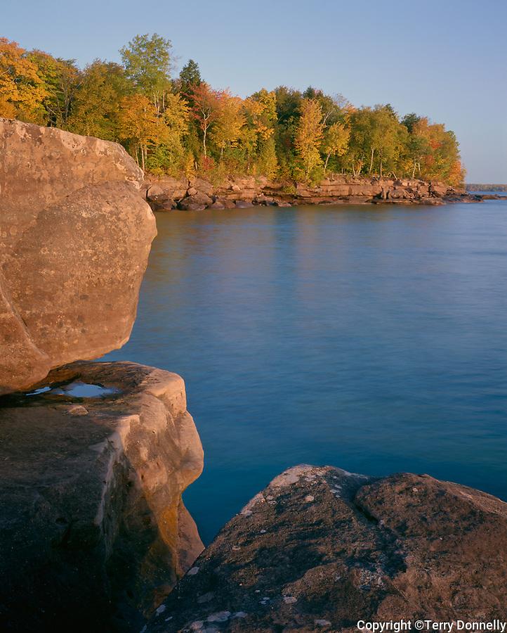 Big Bay State Park, WI: Sunrise light on boulders above Lake Superior, shoreline forest in fall color - Madeline Island, Apostle Islands