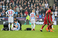 Andre Ayew of Swansea City leads his brother Jordan (R) off the pitch after being shown a red card by referee Michael Oliver for his foul against Jonathan Hogg of Huddersfield who is on the ground during the Premier League match between Huddersfield Town and Swansea City and at the John Smith's Stadium Huddersfield, England, UK. Saturday 10 March 2018