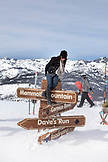 USA, California, Mammoth, a young lady poses on top of one of the lift signs at Mammoth Ski Resort