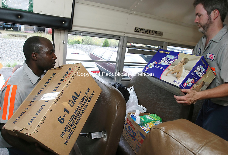 WATERBURY,  CT 16 September 2005 -091605BZ02- First Student mechanics Etienne Brutus, left, and James Hungerford, right, load supplies into one of the school buses that's being driven to Mississippi.  <br />  Jamison C. Bazinet / Republican-American