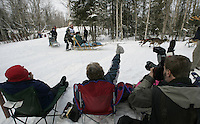 Spectators sit in easy chairs and cheer as Greg Hickmann of McMilan, Michigan rounds a bend on the Anchorage ski/bike trail during Saturday's ceremnial start in Anchorage.