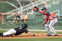 Anderson Franco (13) of the Hagerstown Suns fields a pick-off throw as Nolan Brown (6) of the Kannapolis Intimidators dives back into first base at Kannapolis Intimidators Stadium on May 6, 2018 in Kannapolis, North Carolina. The Intimidators defeated the Suns 4-3. (Brian Westerholt/Four Seam Images)