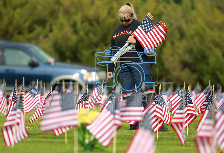 Lynn Reyna reads markers at the Lone Mountain Cemetery in Carson City, Nev., on Friday, May 25, 2012. Volunteers from the D.A.V., American Legion, Carson High School ROTC and Boy Scout Troop 145 placed more than 1,400 flags on the graves of veterans in honor of Memorial Day..Photo by Cathleen Allison