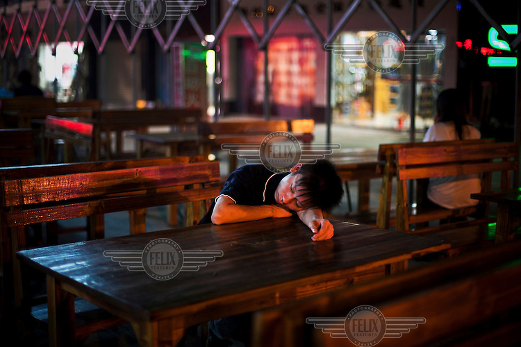 A worker from the nearby Foxconn factory sleeps at a restaurant table after a night of drinking. Foxconn is a Taiwanese technology company that makes products for Apple and Sony among others and is the largest private sector employer in China.