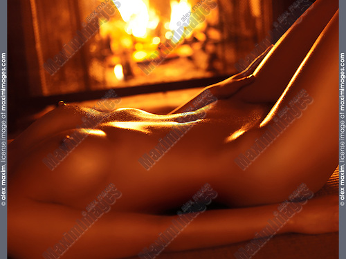Closeup of a beautiful naked woman shiny nude body lying in front of a burning fireplace