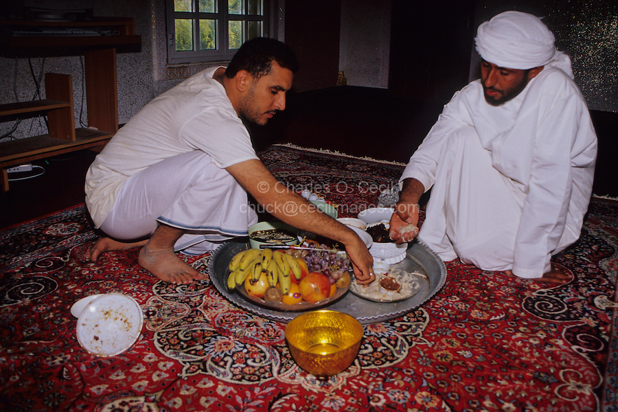 Mudayrib, Oman, Arabian Peninsula, Middle East - Omani Men Taking Lunch on the Eid al-Adha (Feast of the Sacrifice), the annual feast through which Muslims commemorate God's mercy in allowing Abraham to sacrifice a ram instead of his son, to prove his faith.   Eating with the hands is still common in informal Omani society.  The men are eating arsiya, a mixture of rice and meat.