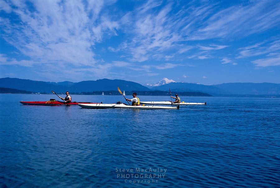Trio of sea kayakers paddle in San Juans with Mount Baker visible behind, San Juan Islands, Washington