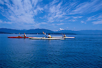 Trio of sea kayakers paddle in San Juans with Mount Baker visible behind, San Juan Islands, Washington