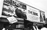 Manhattan, New York City, NY. September 28th, 1966.<br /> Demonstration in front of billboard of the movie &quot;The Bible&quot;, a man is holding a nazi sign with the swastika, protesting against the escalation of the Vietnam War.