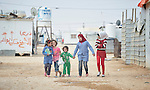 Girls walk to school in the Zaatari refugee camp near Mafraq, Jordan. Established in 2012 as Syrian refugees poured across the border, the camp held more than 80,000 refugees by early 2015, and was rapidly evolving into a permanent settlement. The ACT Alliance provides a variety of services to refugees living in the camp.