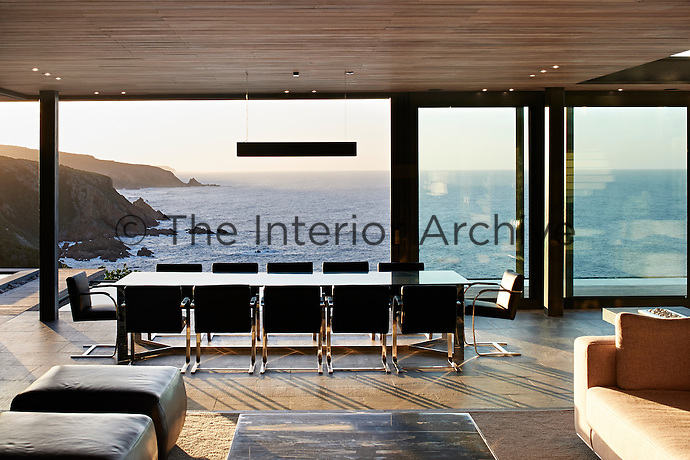 A single dropped light breaks the seamless view of the dramatic African coastal cliffs while the dropped ceiling houses lights, and provides a space division from the larger living spaces.