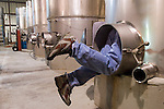 Worker climbs into fermenting tank at winery in Louisiana