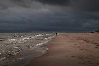 ensam man promenerar på en sandstrand vid havet med mörka moln på Östelen i Skåne