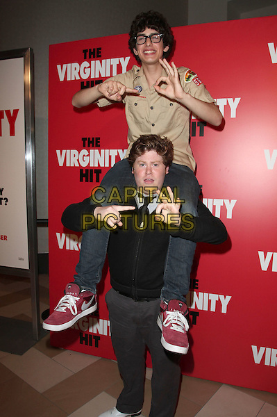 MATT BENNETT & ZACK PEARLMAN.KROQ Screening Of Columbia Pictures' 'The Virginity Hit' held at The Regal Theatres LA Live, Los Angeles, CA, USA, 7th September 2010..half length beige shirt glasses on shoulders piggyback black tie funny carrying rude gesture hand sign re trainers full .CAP/ADM/KB.©Kevan Brooks/AdMedia/Capital Pictures.