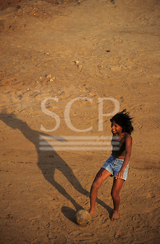 Altamira, Brazil. Football; girl playing football on a sandy road.