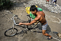A smuggler pushes a bicycle loaded with gasoline barrels on the shore of the river Tachira on the Colombia-Venezuela border, 2 May 2006. Venezuelan gasoline, being 20 times cheaper than in Colombia, is the most wanted smuggling item, followed by food and car parts, while reputable Colombian clothing flow to Venezuela. There are about 25,000 barrels of gasoline crossing illegally the Venezuelan border every day. The risky contraband smuggling, especially during the rainy season when the river rises, makes a living to hundreds of poor families in communities on both sides of the frontier.