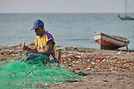 A year after Hurricane Matthew ravaged parts of Haiti, a fisher mends his net on a beach in northwestern Haiti near the village of Plateforme. The village was ravaged in the storm, and Lutheran World Relief, a member of the ACT Alliance, has helped the community rebuild its economy with fishing materials, a solar-powered refrigerator room for storing their catch, and other assistance.