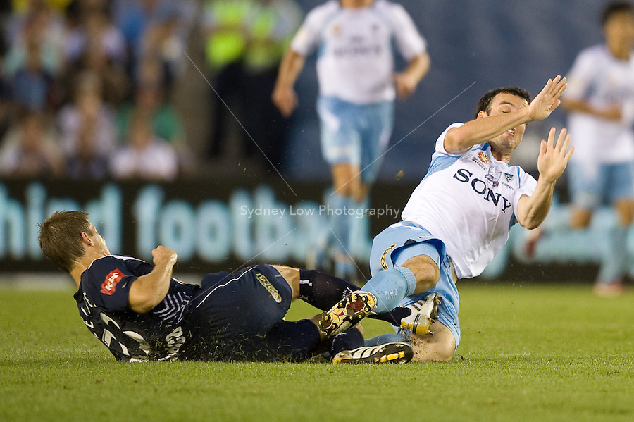 MELBOURNE, AUSTRALIA - MARCH 20, 2010: Adrian Leijer of Melbourne Victory goes in for a tackle against Mark Bridge of Sydney FC in the final of the 2010 A-League between the Melbourne Victory and Sydney FC at Etihad Stadium on March 20, 2010 in Melbourne, Australia. Photo Sydney Low www.syd-low.com