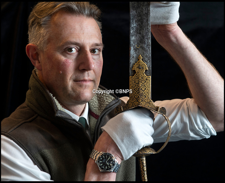 BNPS.co.uk (01202) 558833<br /> Pic: PhilYeomans/BNPS<br /> <br /> 'Once in a lifetime find' Auctioneer Anthony Cribb with the Tiger of Mysore's Firangi sword.<br /> <br /> Stunning artefacts from Indian hero Tipu Sultan's fateful last stand against the British have been rediscovered by the family of an East India Company Major who took part in the Battle that ended his reign in 1799.<br /> <br /> Major Thomas Hart's lucky descendents are now likely to become overnight millionaires after retrieving the historic items from their dusty attic.<br /> <br /> The fascinating treasures were taken from Tipu's captured fortress of Seringapatam in the wake of his defeat by British forces led by a young Duke of Wellington in 1799.<br /> <br /> The cache of ornate arms and personal affects include the battle damaged musket the famous freedom fighter used in his fatal last stand against the expanding British Empire in India.<br /> <br /> Tipu was last seen on the battlements of the fortress firing his hunting musket at the advancing British. After the fierce battle his body was found bearing many wounds including a musket ball shot above his right eye.<br /> <br /> Tipu's recently rediscovered musket, complete with battle damaged bayonet, has the distinctive tiger stripe pattern unique to the self styled Tiger of Mysore - and tellingly there is also shot damage to the lock and stock that may have been caused by the musket ball that finished him off.<br /> <br /> Also included in the sale are four of his ornate gold-encrusted sword's bearing the mark of Haider Ali Khan, Tipu's father and the previous ruler of independent Mysore.<br /> <br /> The war booty was brought back to Britain by Major Thomas Hart of the British East India Company following the fourth and final Anglo-Mysore war.<br /> <br /> They have been passed down through the family and now belong to a couple who have kept them wrapped in newspaper in the dusty attic of their semi-detached home for years.