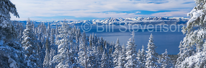 A panorama photo of Lake Tahoe on a winter morning after a snowstorm. Looking west across the lake is the view of Mount Tallac and the west shore. The best time to shoot snow on trees is while a storm is clearing. You can see the lake-level clouds still lingering on the far shore.