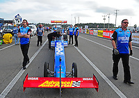 Mar. 10, 2012; Gainesville, FL, USA; Crew members stand alongside the car of NHRA top fuel dragster driver T.J. Zizzo during qualifying for the Gatornationals at Auto Plus Raceway at Gainesville. Mandatory Credit: Mark J. Rebilas-