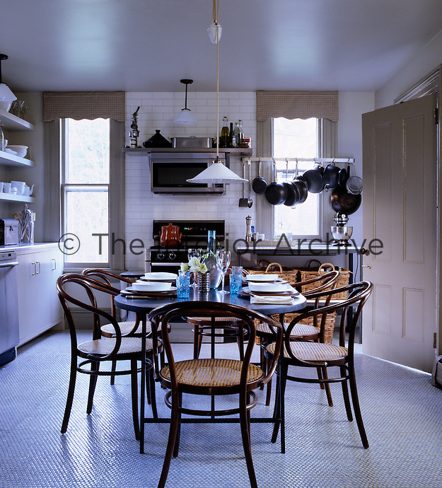 Vintage bentwood Thonet chairs and a slate-topped steel table form the centrepiece of this kitchen