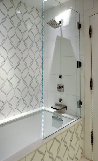 This custom shower features Sophie, a handmade mosaic shown in polished Calacatta Tia and honed Thassos, a part of the Silk Road Collection by Sara Baldwin for New Ravenna.<br />