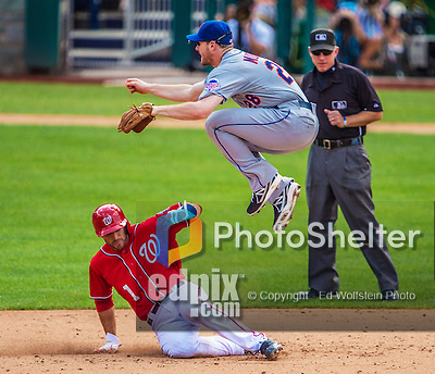 26 July 2013: New York Mets infielder Daniel Murphy jumps over Stephen Lombardozzi in a double play against the Washington Nationals at Nationals Park in Washington, DC. The Mets shut out the Nationals 11-0 in the first game of their day/night doubleheader. Mandatory Credit: Ed Wolfstein Photo *** RAW (NEF) Image File Available ***