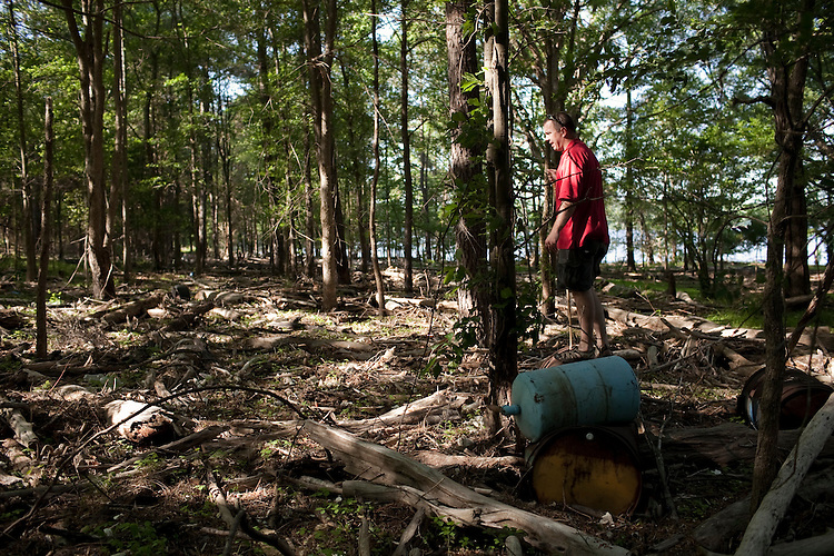 Colson walks over a thick bed of debris made of plastic bottles, tires, trees, and anything that has floated down the Haw River to be left at the common high water mark of Jordan Lake - which is sometimes far from the wooded shoreline.