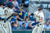 Michigan Wolverines shortstop Jack Blomgren (2) is greeted by teammate Jordan Nwogu (42) after scoring against the Vanderbilt Commodores during Game 1 of the NCAA College World Series Finals on June 24, 2019 at TD Ameritrade Park in Omaha, Nebraska. Michigan defeated Vanderbilt 7-4. (Andrew Woolley/Four Seam Images)