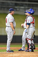 Tennessee Smokies pitching coach Storm Davis (34) talks with pitcher Jeff Lorick (25) and catcher Taylor Davis (27) during a game against the Birmingham Barons on April 22, 2014 at Regions Field in Birmingham, Alabama.  Birmingham defeated Tennessee 14-3.  (Mike Janes/Four Seam Images)