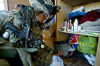 A US soldier from second platoon, Alfa company, 1st battalion, 506th, 101st airborne division searches through the personal belongings of an iraqi man who will be later held by the US military to be interrogated while executing OPERATION TEEN WOLF, a raid in a neighborhood of western Ramadi with the purpose of searching for insurgency weapons, gather intel and meet with the civilian population, in the city of Ramadi, Iraq on Tuesday January 03 2006. during the raid four suspected Sunni insurgents were held  by the US military for further interrogations.