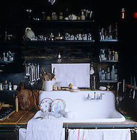 Detail of the enamel kitchen sink surrounded by open shelving crammed with glass jars