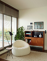 The living room has a strong retro feel, in keeping with the Bauhaus architecture of the building.  In one corner stands a Noe Duchaufour-Lawrance chair, alongside is a home-made table. Next to the chair is a Greta Grossman Grasshopper floor lamp and against the wall stands a vintage display cabinet. The floor to ceiling window is dressed with a wood venetian blind.