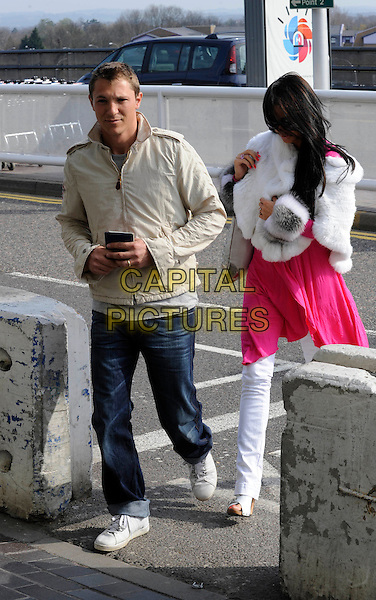 ANDREW GOULD & KATIE PRICE (aka JORDAN).Leaving Gatwick Airports North Terminal, Sussex, England..April 13th, 2010.full length white jeans denim fur wrap pink top dress looking down hiding covering face beige jacket.CAP/FIN.©Steve Finn/Capital Pictures.