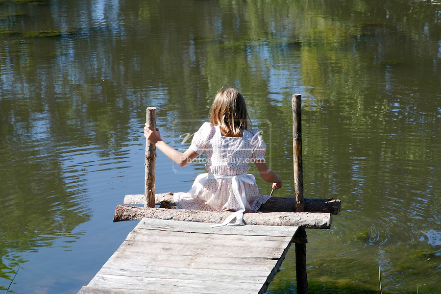 A young girl sitting on an old fashioned pier by a pond